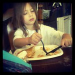 Cutting her food like a lady