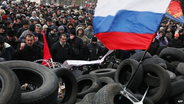 Pro-Russian activists rally at a barricade outside the regional state administration in the eastern Ukrainian city of Donetsk, 11 April 2014