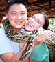Kelly Westhoff and Quang Nystrom with a boa constrictor in Cambodia