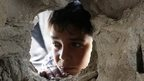 A boy looks through a hole on the wall made by the shelling at the Abu Hussein U.N. school in the Jebaliya refugee camp in the northern Gaza Strip on Wednesday, July 30, 2014