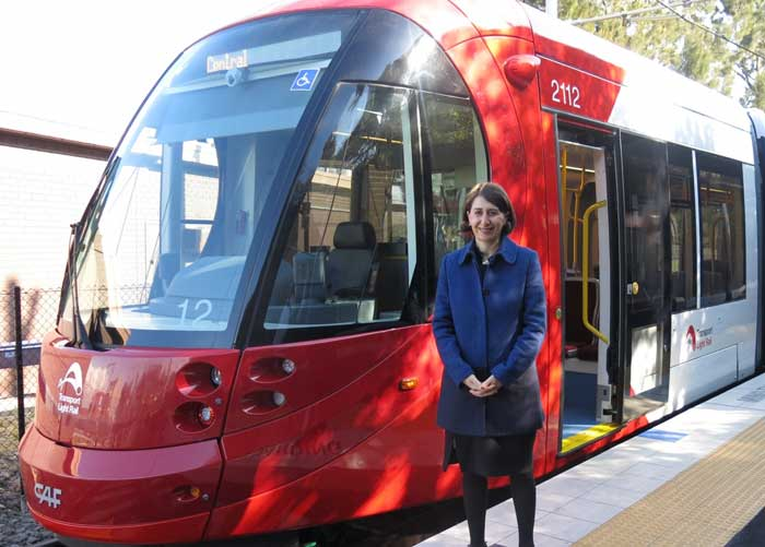 NSW Minister for Transport Gladys Berejiklian standing beside a new light rail vehicle