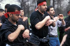 Shi'a men wearing red headbands in an Ashura parade