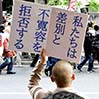 """A protester holds a placard that reads, """"We refuse to allow discrimination and intolerance,"""" while a group of demonstrators calling for the ouster of foreigners march in Tokyo's Shinjuku Ward in April 2013. (Asahi Shimbun file photo)"""