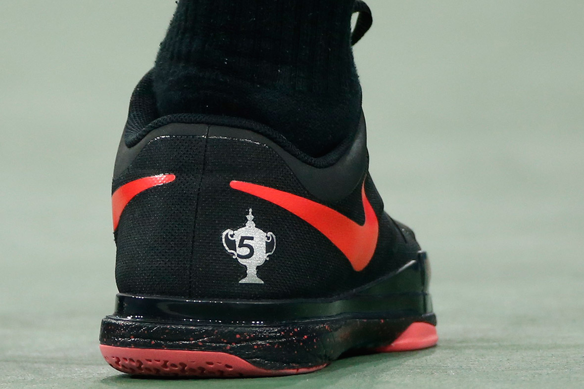 Roger Federer of Switzerland wears a shoe noting his five US Open titles as he comes from behind to defeat Gael Monfils of France during their quarter-final men's singles match