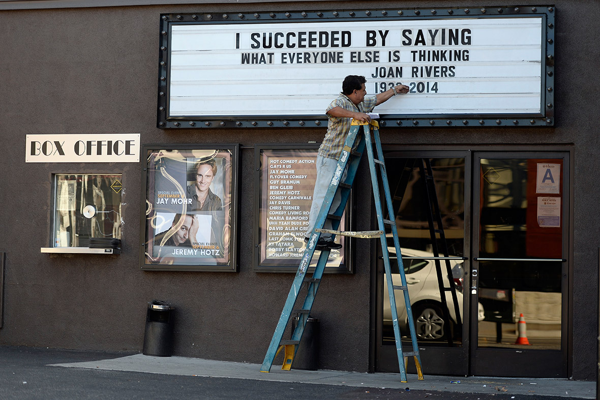 A worker changes the marquee at the Improv comedy club in Los Angeles to display a quote from the late comedian Joan Rivers