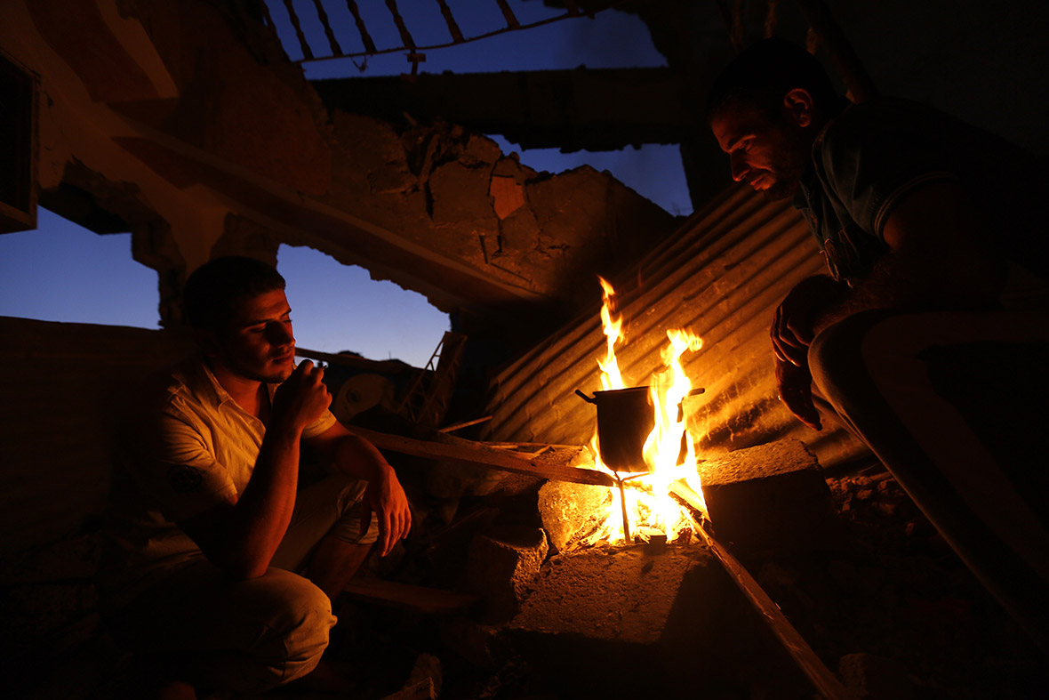 Palestinian men boil water amid the rubble of destroyed houses in the Shejaiya neighbourhood of Gaza City