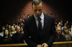 File photo of Oscar Pistorius standing in the dock ahead of court proceedings at the Pretoria magistrates court