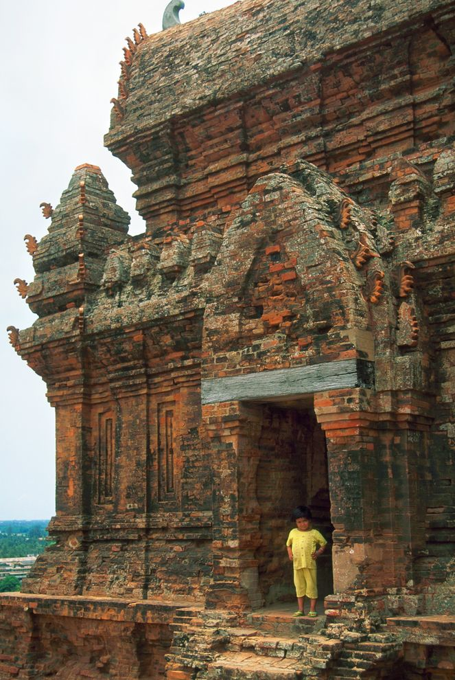 Photo of a child standing in the doorway of a Cham Hindu temple.