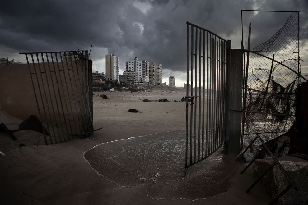 Gaza City apartments rise beyond the broken gates of a waterfront restaurant. The beach once bustled with fishing boats and cafés, but the Israeli naval blockade, sewage, and lack of resources for rebuilding have taken their toll.