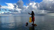 Eine Frau fängt Fische an der Küste von Bikeman Island. Die Insel gehört zu Kiribati. Der Pazifikstaat könnte in 60 Jahren unbewohnbar sein. Grund ist der steigende Meeresspiegel.