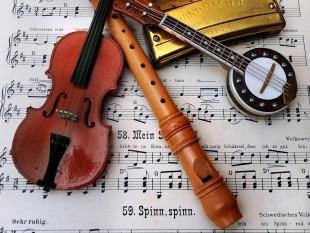 Eine Geige, eine Flöte, eine Mundharmonika und ein Banjo liegen auf einem Notenblatt.