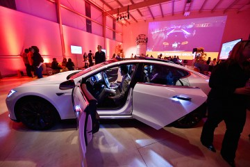 "Tesla owners look at the interior of the Tesla ""D"" electric sedan after Elon Musk unveiled the dual-engine chassis—a faster, all-wheel-drive version of the Model S"