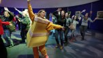 """Joanna Truglio, of Macy's.com creative production, who will be in her fourth Thanksgiving Day Parade, wears her cake-slice costume as she schools volunteers, and other Macy's employees during """"Clown U."""" at the the Big Apple Circus, in New York's Lincoln Center, Saturday, Nov. 15, 2014. A one-day training session was held for people who want to be among the thousand or so clowns in the Thanksgiving Day Parade. (AP Photo/Richard Drew)"""