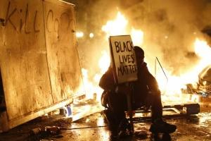 A demonstrator sits in front of a street fire in Oakland.  REUTERS/Stephen Lam