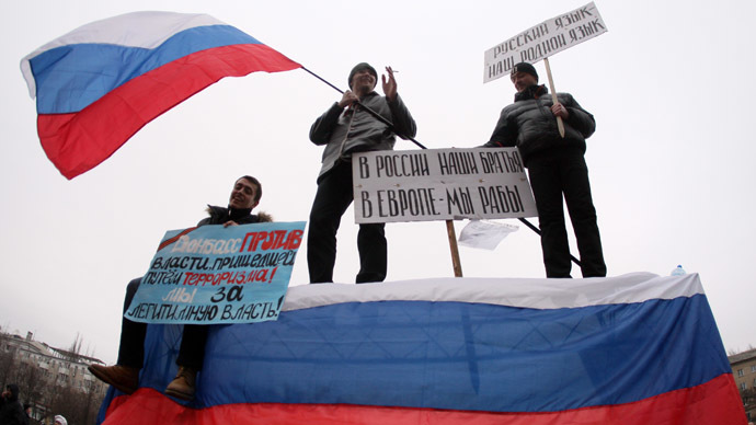 """Pro-Russian protesters wave a Russian flag and hold a sign (C) reading """"Our brothers are in Russia, we are slaves in Europe"""" during a rally in front of the regional administration building in the industrial Ukrainian city of Donetsk on March 1, 2014. (AFP Photo)"""