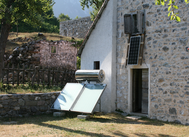 Solar powered water heater sits in the sun next to a stone house in Albania
