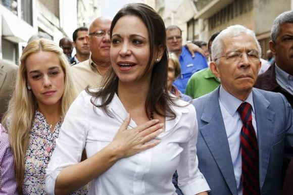 Venezuela's opposition leader Maria Corina Machado (C) gestures next to Lilian Tintori (L), wife of jailed opposition leader Leopoldo Lopez, as Machado arrives under a subpoena at a court in Caracas June 16, 2014.     REUTERS/Carlos Garcia Rawlins
