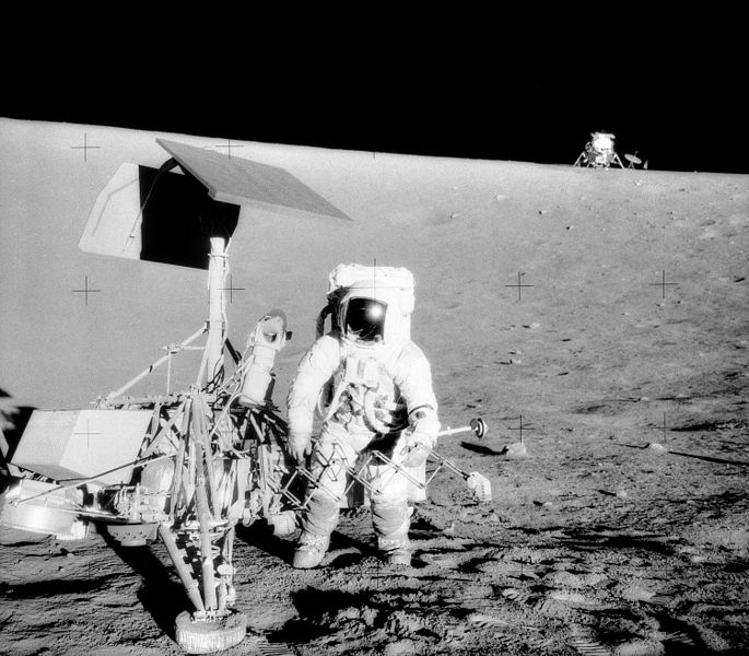"""Charles Conrad Jr., Apollo 12 Commander, examines the unmanned Surveyor III spacecraft during the second extravehicular activity (EVA-2). The Lunar Module (LM) """"Intrepid"""" is in the right backgroun"""