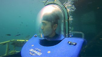 Henry Golding wears a diving suit underwtaer