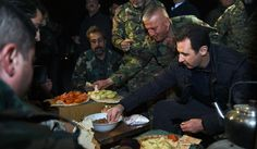 In this Wednesday, Dec. 31, 2014 photo released by the Syrian official news agency SANA, Syrian President Bashar Assad, right, shares a meal with Syrian troops during his visit on the front line in the eastern Damascus district of Jobar, Syria. Assad has made a rare visit to the front line of his country's civil war, spending New Year's Eve with his troops in a tense eastern Damascus neighborhood. (AP Photo/SANA)