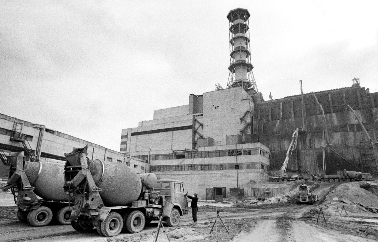Trucks filled with concrete wait for unloading at the construction site of the concrete sarcophagus over reactor 4.