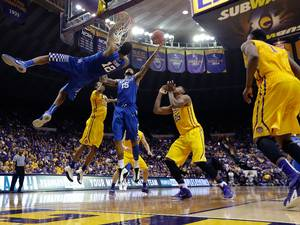 10 February 2015: Kentucky forward Karl-Anthony Towns (12) is called for a technical for hanging on the rim while forward Willie Cauley-Stein (15) tries to tip it in, after Towns' slam dunk bounced out, in the second half of an NCAA college basketball game against LSU in Baton Rouge. Kentucky won 71-69. Behind are LSU forward Jordan Mickey (25), guard Tim Quarterman (55) and forward Jarell Martin (1)