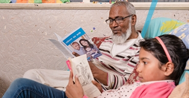 Kolomdor, who has Parkinson's, reading a leaflet with his daughter
