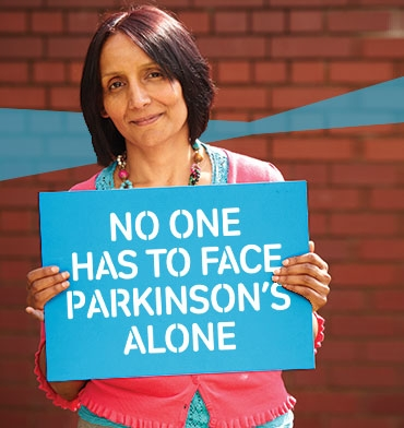 Ramilla holding placard saying 'No one has to face Parkinson's alone'