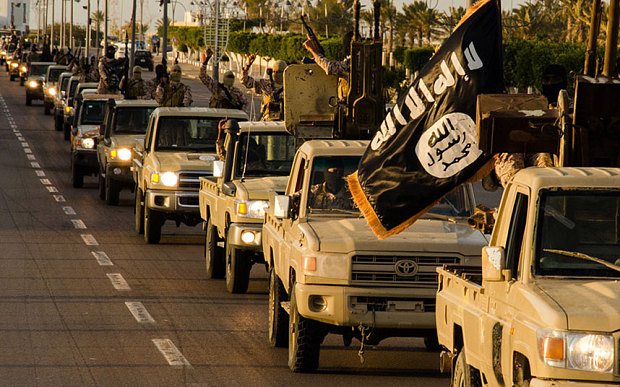 members of the Islamic State (IS) militant group parading in a street in Libya's coastal city of Sirte