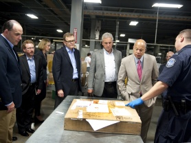 Secretary Johnson inspects incoming international packages at UPS Worldport Facility with UPS Vice President of Government Affairs Norm Schenk and UPS Chief Operating Officer and incoming Chief Executive Officer David Abney