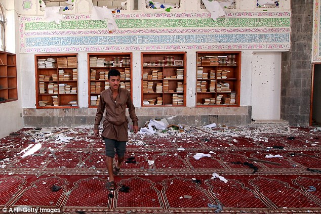 A Yemeni man inspects the damage following one of the explosions. Glass and debris can be seen all over the floor but prayer books remain on the shelves