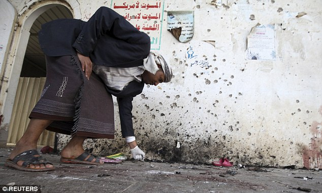 A crime-scene investigator examines the ground following the bomb blasts in Sanaa. It was one of the country's deadliest ever jihadist attacks