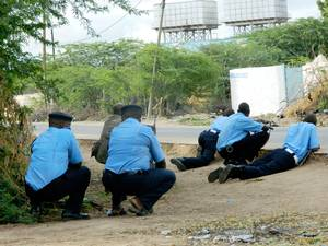 Kenyan police officers take cover outside the Garissa University College during an attack by gunmen in Garissa