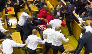 Members of Julius Malema's Economic Freedom Fighters (EFF) clash with security officials after being ordered out of the chamber during President Jacob Zuma's State of the Nation address in Cape Town
