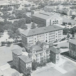 The old B. Hall stands in front of Waggener Hall, with Gregory Gym in the distance