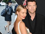 """Actors Lara Bingle (L) and Sam Worthington attend the Los Angeles premiere of """"Sabotage"""" at Regal Cinemas LA Live in Los Angeles, California, March 19, 2014.  AFP PHOTO / ROBYN BECK        (Photo credit should read ROBYN BECK/AFP/Getty Images)"""