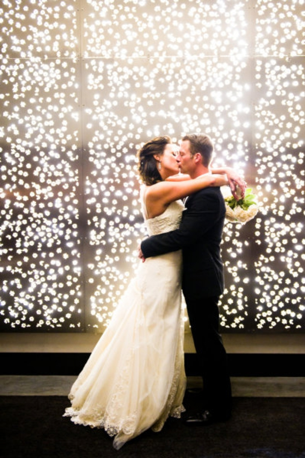 bride and groom kissing in front of wall of twinkle lights