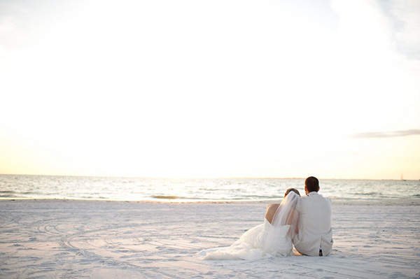 bride and groom sitting together in the sand watching the sunset on Fort Myers Beach, romantic Christmas beach wedding, Luminaire Foto