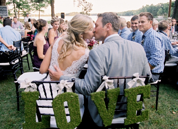 bride and groom first kiss at reception, moss covered letters spelling love, chair decor, Rustic Wisconsin Resort Wedding, Emily Steffen Photography
