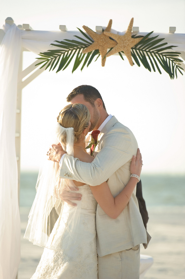 first kiss as husband and wife, simple beach decorated wedding arch, starfish and palm frond wedding arch decor, Luminaire Foto