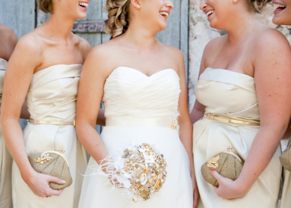 gold colored bridesmaids dresses with glittery belts and clutches, white and gold brooch bouquet, rustic wedding fashion