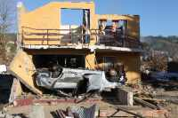 A house and a car were destroyed by a tsunami in the coastal city of Dichato, Chile, located about 15 km north of Concepcion, Chile. The tsunami height was about 10 meters (32 feet). Several hundred homes were destroyed in this city as a result of the M 8