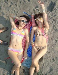 2 foto cewek abg memakai bikini berbaring di pantai
