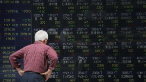 A man walks past an electronic stock board of a securities firm in Tokyo on May 14, 2015. (AP / Eugene Hoshiko)