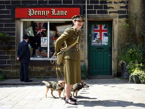 15 May 2015: A woman dressed as a member of British Home Guard from World War II laughs as she attempts to unfurl her tangled dog leads on the first day of the Haworth 1940s Weekend in the village of Haworth, Northern England