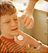 Father putting ointment on boy's face