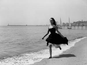 Actress Brigitte Bardot running barefoot along the beach, Cannes, France, April 28th 1956
