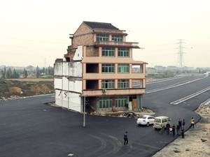 A half-demolished apartment building standing in the middle of a newly-built road thanks to a Chinese couple that refused to move in Wenling, in eastern China's Zhejiang province. Luo Baogen, 67, and his 65-year-old wife have waged a four-year battle to receive more than the 41,300 USD compensation offered by the local government of Daxi, a Chinese newspaper said. The phenomenon is called a 'nail house' in China, as such buildings stick out and are difficult to remove, like a stubborn nail