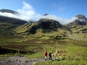 12 June 2015: Hillwalkers set out towards the Three Sisters mountain range in Glencoe in the Highlands of Scotland