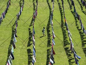 12 June 2015: A women walks amid thousands of dresses hanging on clotheslines set-up at the Pristina Stadium, as part of an installation
